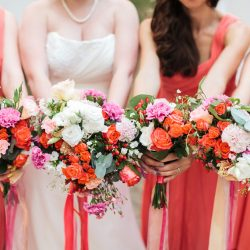 bride and bridesmaids show off wedding bouquets