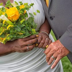 bride and groom show off rings and wedding flowers