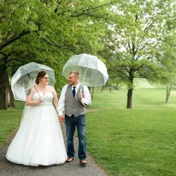 bride and groom walk in the rain